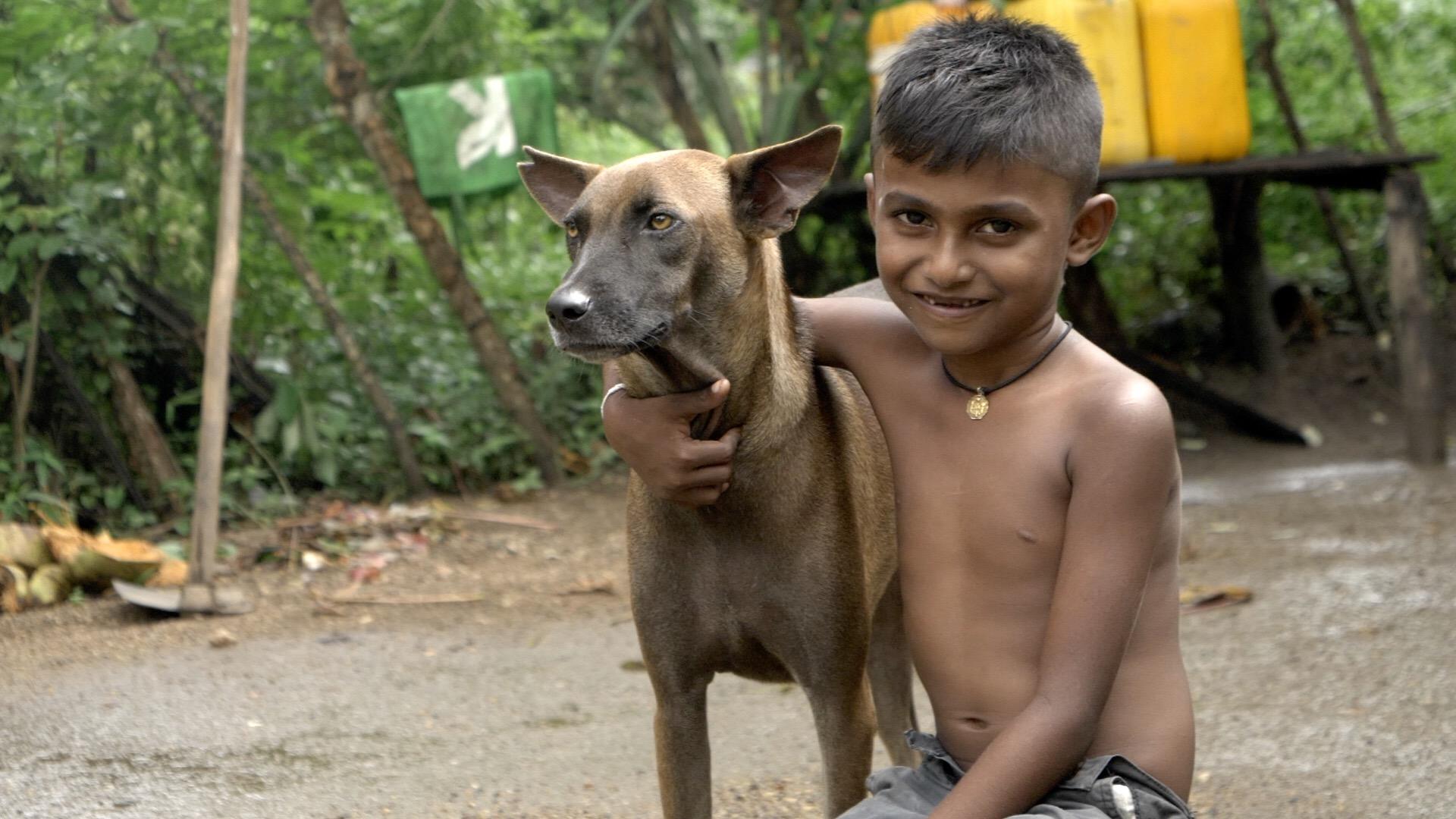 Sri Lankan boy with dog, still from Alex Gatenby film